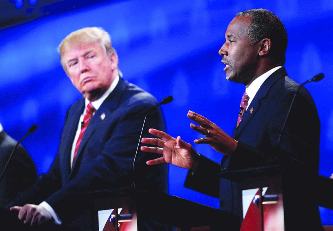 Republican U.S. presidential candidate businessman Donald Trump (L) listens as Dr. Ben Carson (R) speaks at the 2016 U.S. Republican presidential candidates debate held by CNBC in Boulder, Colorado, October 28, 2015. REUTERS/Rick Wilking