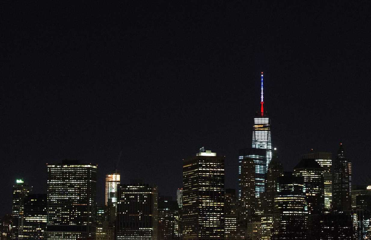 NEW YORK, NY - NOVEMBER 13: One World Trade Center's spire is shown lit in French flags colors of white, blue and red in solidarity with France after tonight's terror attacks in Paris, November 13, 2015 in New York City. According to reports, over 150 people were killed in a series of bombings and shootings across Paris, including at a soccer game at the Stade de France and a concert at the Bataclan theater. (Photo by Daniel Pierce Wright/Getty Images)