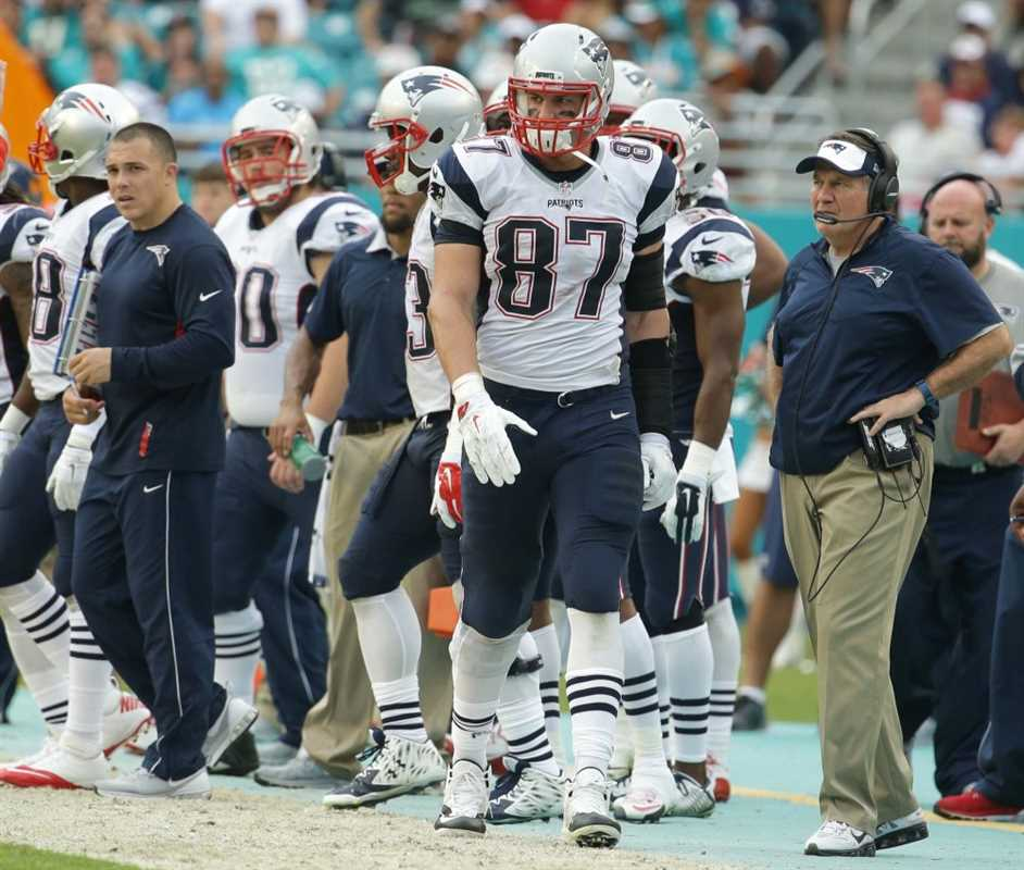 New England Patriots tight end Rob Gronkowski (87) and head coach Bill Belichick, right, walk the sidelines during the second half of an NFL football game, Sunday, Jan. 3, 2016, in Miami Gardens, Fla. The Dolphins defeated the Patriots 20-10. (AP Photo/Lynne Sladky) ORG XMIT: SLS123